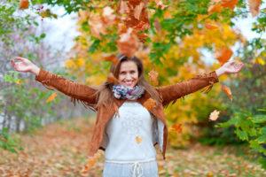 Chica rodeada de hojas otoñales. Moda básica de otoño.